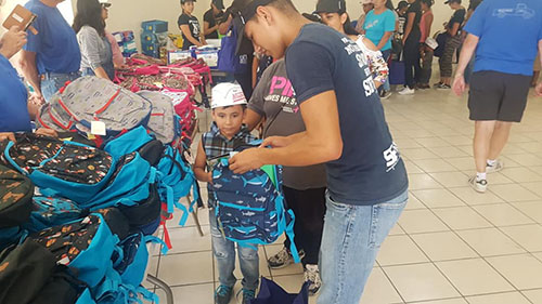 Children receiving book bags that were donated